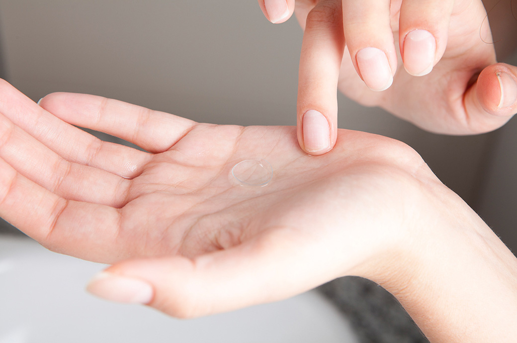 Someone's hands with a contact lens on her palm