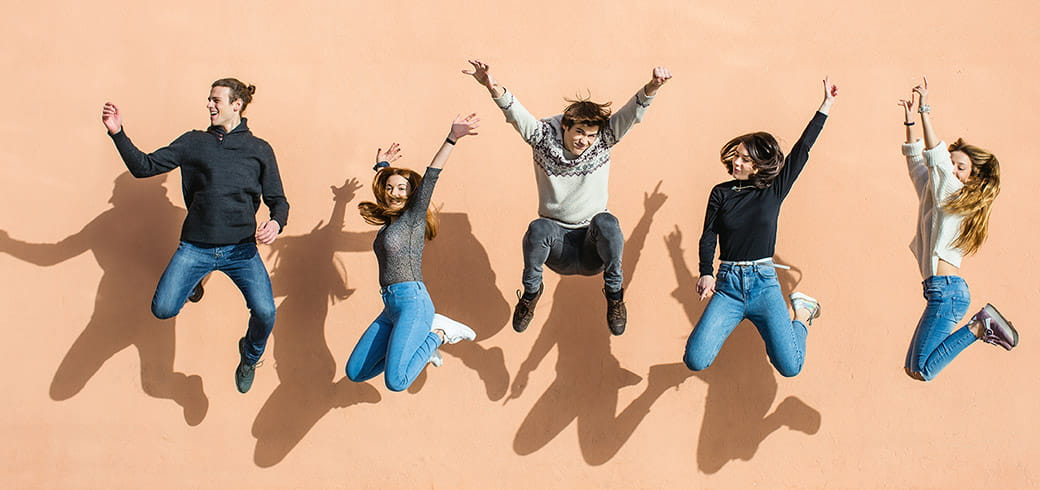 A group of friends jumping in the air, laughing and smiling.