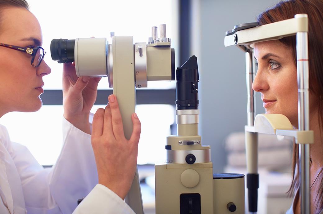 Πλαϊνή άποψη ενός εφαρμοστή και μιας νεαρής γυναίκας που κοιτά μέσα σε μια αμφιβληστροειδική κάμερα
