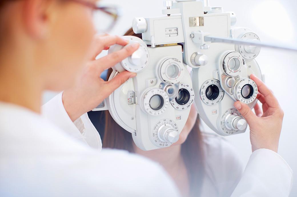 Μια νεαρή γυναίκα πίσω από ένα φορόπτερο, καθώς ο εφαρμοστής εξετάζει τα μάτια της κατά τη διάρκεια μιας οφθαλμικής εξέτασης.