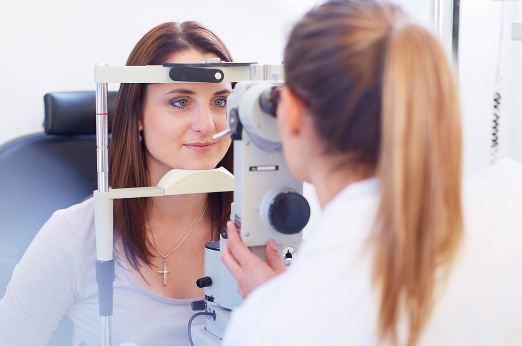 Η κάμερα εστιάζει σε μια νεαρή γυναίκα που κοιτάζει μέσα σε μια αμφιβληστροειδική κάμερα καθώς ο επαγγελματίας υγείας των ματιών της κοιτάζει από την άλλη πλευρά